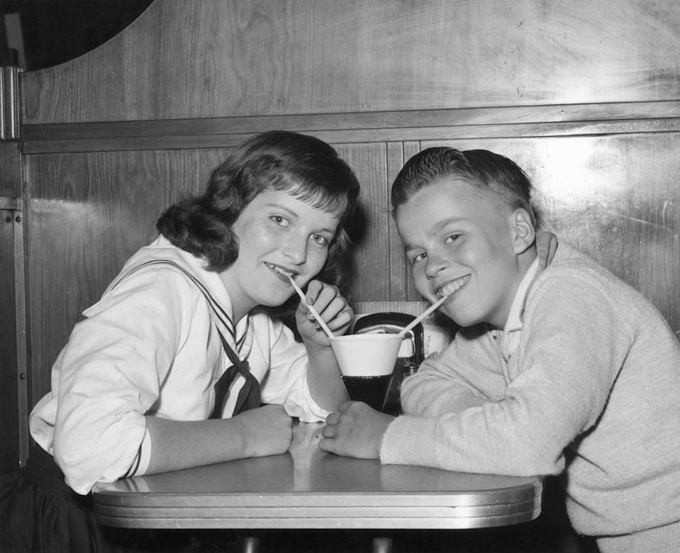 <p>A boy and girl sip from a single treat as they pose for a picture.</p>