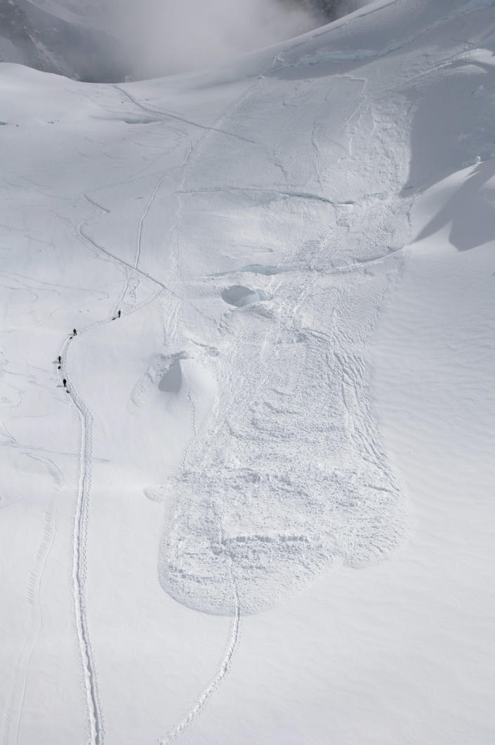 In this Friday, June 15, 2012 photo provided by the National Park Service, climbers hike through the area where an avalanche swept a Japanese climbing team off a hill during their descent from Alaska's Mount McKinley. U.S. National Park Service officials say five people were traveling as a one rope team early Thursday morning as part of a Miyagi Workers Alpine Federation expedition on the Alaska mountain. The NPS said Hitoshi Ogi, 69, survived after falling 60 feet (18 meters) into a crevasse. He was able to climb out. The other four tumbled into the avalanche debris and haven't been seen since. (AP Photo/National Park Service, Kevin Wright)