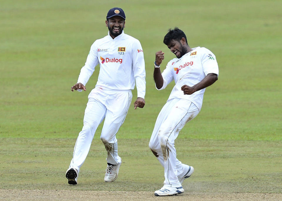 Sri Lanka's Ramesh Mendis, right, celebrates with teammate Dimuth Karunaratne the dismissal of Bangladesh's Najmul Hossain during the third day of the second cricket test match between Sri Lanka and Bangladesh in Pallekele, Sri Lanka, Sunday, May 01, 2021. ( AP Photo/Sameera Peiris)
