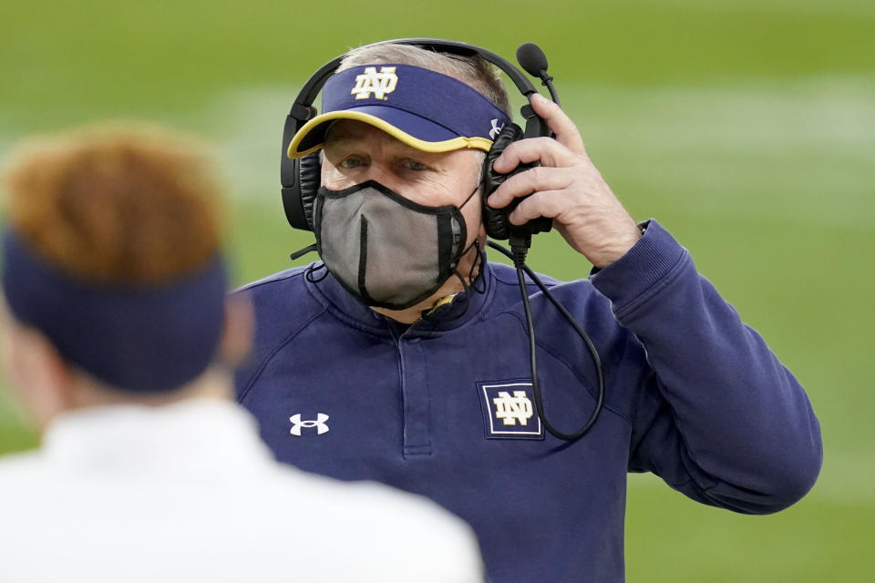 Notre Dame head coach Brian Kelly adjusts his headset as he walks to talk to Jonathan Doerer during the second half of an NCAA college football game against Pittsburgh, Saturday, Oct. 24, 2020, in Pittsburgh. (AP Photo/Keith Srakocic)