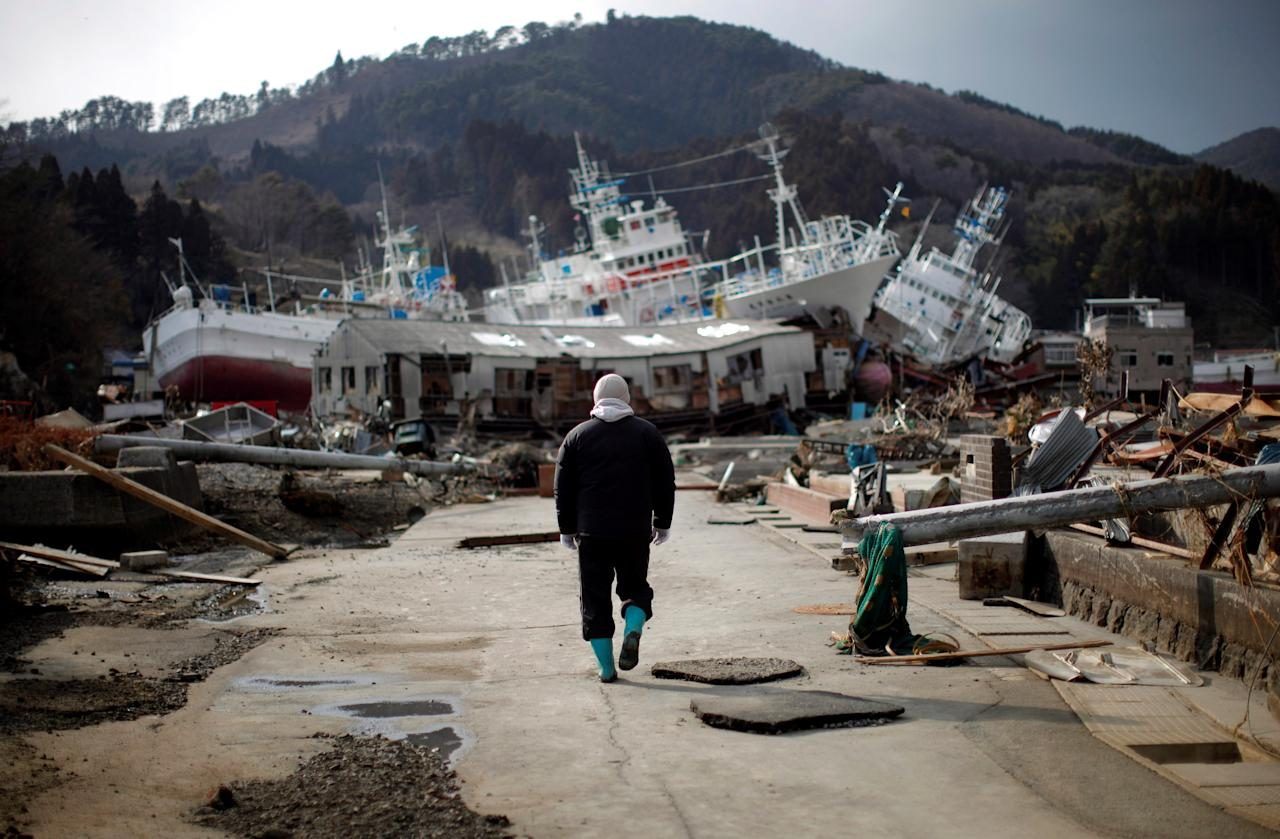 FILE PHOTO: A man walks next to port area destroyed by the earthquake and tsunami in Kessenuma town, in Miyagi prefecture March 28, 2011.  REUTERS/Carlos Barria/File Photo