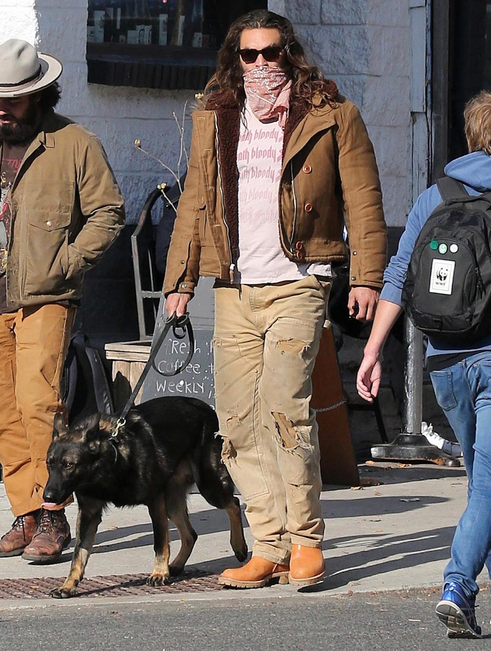 <p>Jason Momoa takes his German Shepard Rama out for a walk on Monday in Toronto.</p>