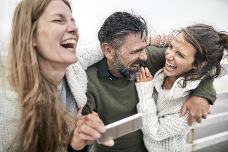 Laughing man and two women with smartphone by the sea