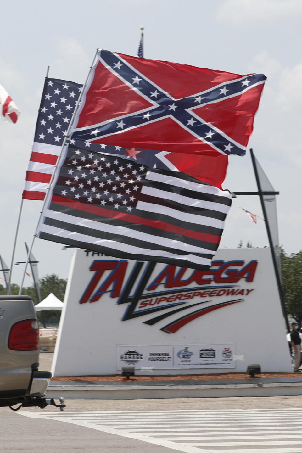 Race fans fly Confederate battle flags and United States flags as they drive by the entrance to Talladega Superspeedway prior to a NASCAR Cup Series auto race in Talladega Ala., Sunday, June 21, 2020.. (AP Photo/John Bazemore)