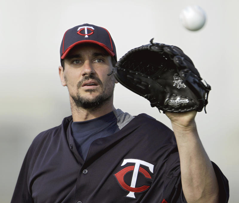 """FILE - In this Feb. 21, 2012 file photo, Minnesota Twins pitcher Carl Pavano works out during baseball spring training in Fort Myers, Fla. Police in Connecticut have searched the home of a high school classmate of  Pavano while investigating an alleged extortion attempt against Pavano. A search warrant affidavit obtained by the Record-Journal of Meriden on Wednesday, March 28, 2012, says Pavano's family told police that 36-year-old Christian Bedard of Southington, Conn.,  tried to extort money and a luxury SUV from Pavano by threatening to publicly reveal a three-year """"emotional and physical relationship"""" the two had while attending Southington High School. (AP Photo/David Goldman, File)"""