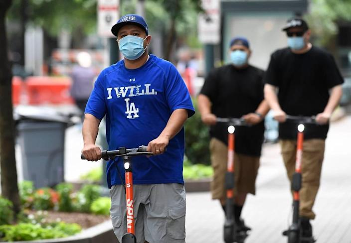 Scooter riders head up the sidewalk along Tryon Street in uptown Charlotte ,while wearing masks, on Wednesday, June 24, 2020. North Carolina Gov. Roy Cooper announced Wednesday the state will remain in Phase Two for another three weeks while making face coverings mandatory in public.