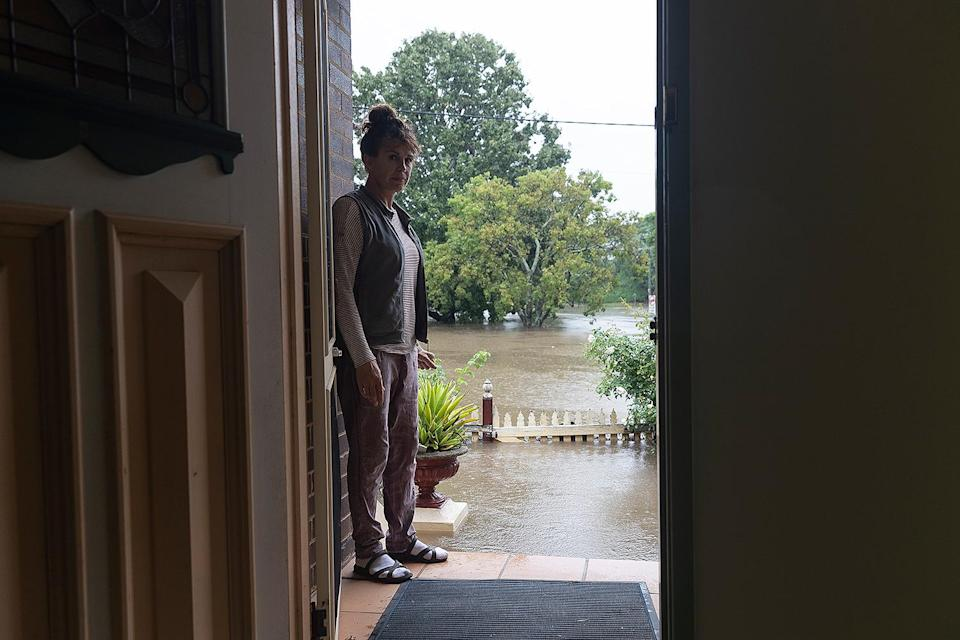 <p>A woman in Windsor shows the flood levels at her door as waters rise near the 100-year-old property.</p>