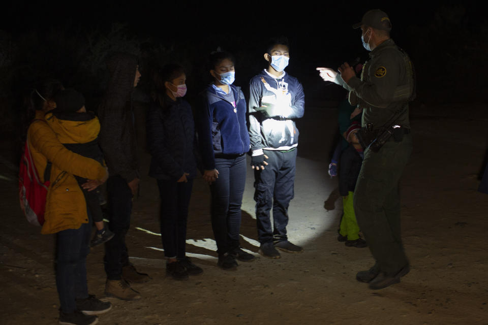 FILE - In this March 28, 2021 file photo Migrants from Guatemala and Honduras are questioned by a Border Patrol agent after being smuggled on an inflatable raft in Roma, Texas. The Biden administration says families arriving at the U.S. border with Mexico will have their cases fast-tracked in immigration court, an announcement on Friday, May 28, that comes less than two weeks after said it was easing pandemic-related restrictions on seeking asylum. Under the plan, immigration judges in 10 cities will aim to decide cases within 300 days. (AP Photo/Dario Lopez-Mills, File)