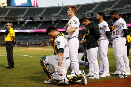 Bruce Maxwell of the Oakland Athletics kneels during the singing of the National Anthem before his MLB American League baseball game against the Seattle Mariners at Oakland-Alameda County Coliseum in Oakland, California, U.S., September 25, 2017. REUTERS/Stephen Lam