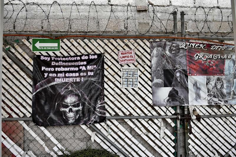 """Posters of Santa Muerte (Holy Death) read: """"I protect delinquents, but robbing me and in my house is your death"""" at a sanctuary in Santa Maria Cuautepec, Tultitlan, Mexico on February 7, 2016 (AFP Photo/Yuri Cortez)"""