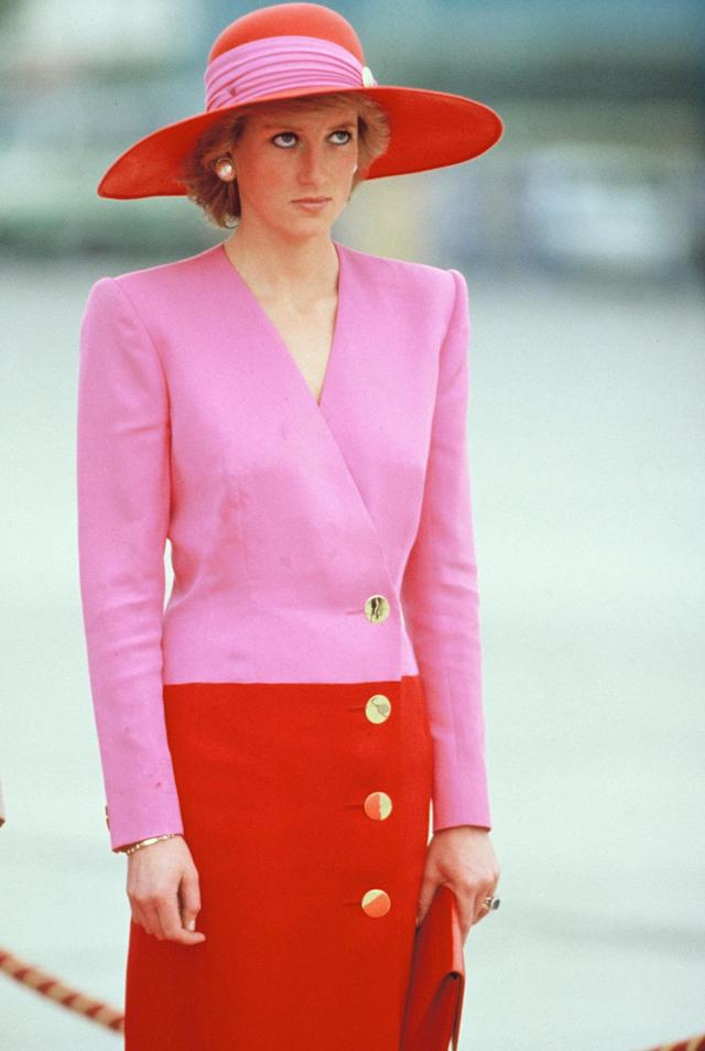 <p>Mixing two bold colors, known as color blocking, was a signature Diana look. Here she wears a Catherine Walker suit in bright pink and red. (Photo: Georges De Keerle/Getty Images) </p>