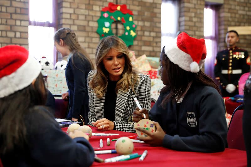 U.S. first lady Melania Trump joins local school students creating holiday decorations at the Salvation Army Clapton Center in London