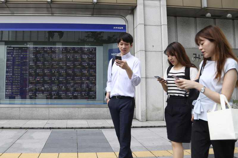 People walk by an electronic stock board of a securities firm in Tokyo, Tuesday, Aug. 20, 2019. Asian shares were mostly higher Tuesday after Wall Street rallied on the U.S. decision to give Chinese telecom giant Huawei another 90 days to buy equipment from American suppliers. (AP Photo/Koji Sasahara)