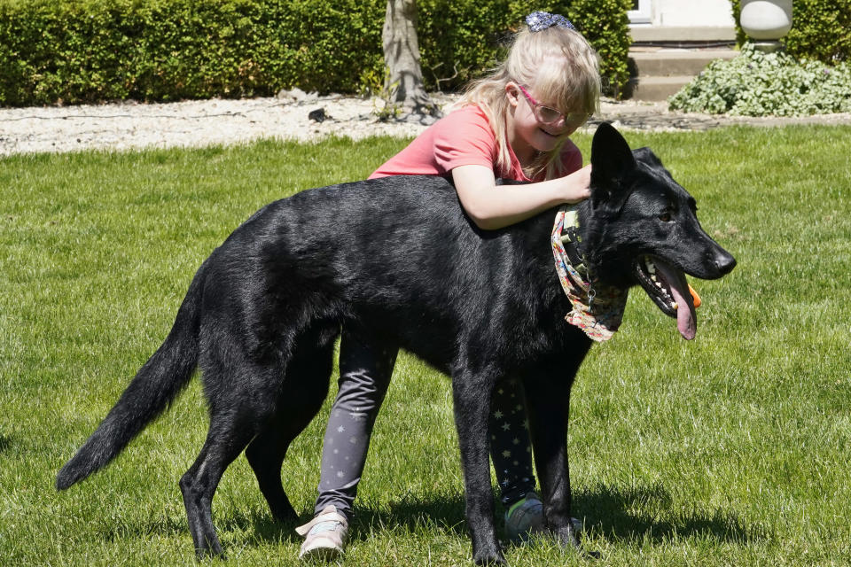 Lyra Christensen hugs her dog, Otto, Thursday, May 13, 2021, in Akron, Ohio. Anti-abortion activists say 2021 has been a breakthrough year for legislation in several states seeking to prohibit abortions based on a prenatal diagnosis of Down syndrome. Opponents of the bills, including some parents with children who have Down syndrome like Lyra's mother Holly, argue that elected officials should not be meddling with a woman's deeply personal decision on whether to carry a pregnancy to term after a Down syndrome diagnosis. (AP Photo/Tony Dejak)
