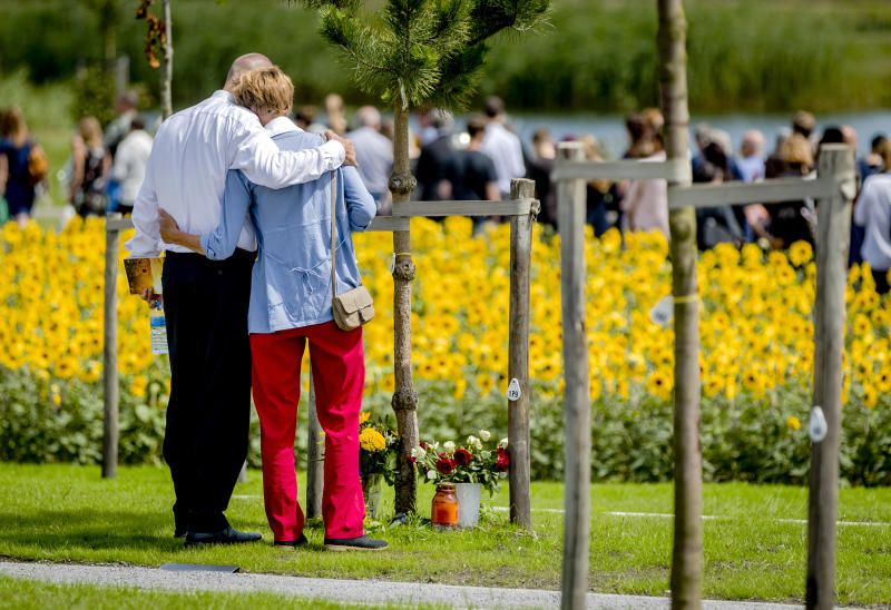Relatives embrace during the revealing of the National Monument for the MH17 victims in Vijfhuizen, The Netherlands, Monday, July 17, 2017. Relatives and friends of people killed 3 years ago when a surface-to-air missile blew a Malaysia Airlines passenger jet out of the sky over Ukraine are marking the anniversary together with the Dutch king at a new memorial near the Amsterdam airport from which the plane departed. (Remko de Waal/ Pool via AP)