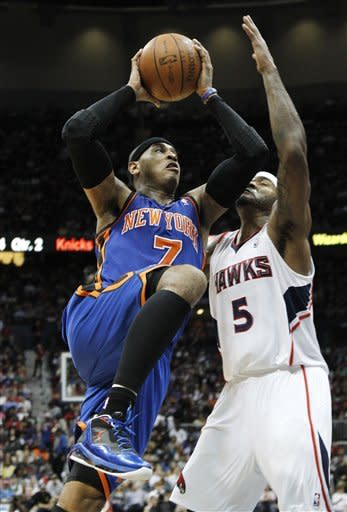 New York Knicks forward Carmelo Anthony (7) drives against Atlanta Hawks forward Josh Smith (5) in the first half of an NBA basketball game on Friday, March 30, 2012, in Atlanta. (AP Photo/John Bazemore)