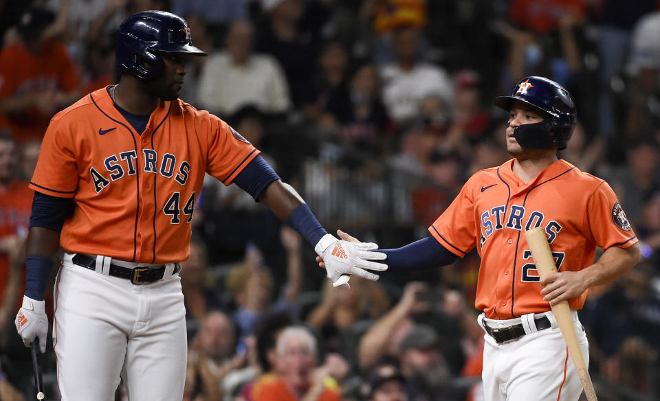 Houston Astros' Jose Altuve, right, celebrates with teammate Yordan Alvarez after scoring a run during the third inning of a baseball game against the Los Angeles Angels, Friday, Sept. 10, 2021, in Houston. (AP Photo/Eric Christian Smith)