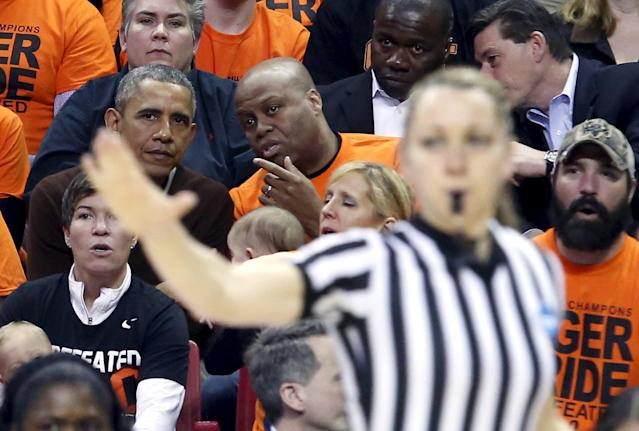 U.S. President Barack Obama (L) attends the game between Princeton and Green Bay for the 2015 Women's NCAA Basketball Tournament at the XFINITY Center in College Park, Maryland March 21, 2015. Obama's niece Leslie Robinson plays for Princeton. REUTERS/Yuri Gripas