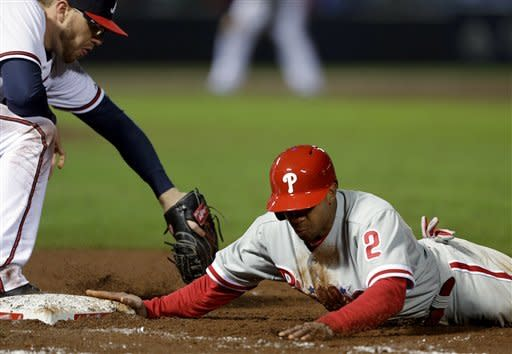 Philadelphia Phillies' Ben Revere, right, dives to beat the tag by Atlanta Braves first baseman Freddie Freeman in the ninth inning of a baseball game, Thursday, April 4, 2013, in Atlanta. Philadelphia won 2-0. (AP Photo/David Goldman)
