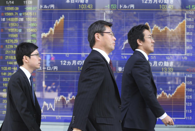 People walk by an electronic stock board of a securities firm in Tokyo, Tuesday, Jan. 14, 2014. Most Asian stock markets sank Tuesday, led by Japan, following a big sell-off in the U.S. (AP Photo/Koji Sasahara)