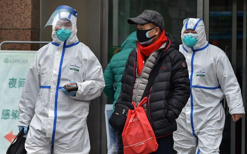 Medical staff wearing clothing to protect against a previously unknown virus walk outside a hospital in Wuhan - AFP