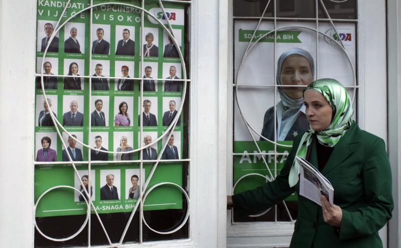 This Oct. 16, 2012 photo shows Amra Babic, mayor of the Bosnian town of Visoko, closes a door plastered with her election posters, in Visoko, 30 km north of Sarajevo, Bosnia. The 43 year-old economist has blazed a trail in this war-scarred Balkan nation by becoming its first hijab-wearing mayor, and possibly the only one in Europe. Her victory comes as governments elsewhere in Europe debate laws to ban the Muslim veil, and Turkey, another predominantly Islamic country seeking EU membership, maintains a strict policy of keeping religious symbols out of public life. For Babic, the electoral triumph is proof that observance of Muslim tradition is compatible with Western democratic values. (AP Photo/Amel Emric)