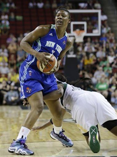 Seattle Storm's Camille Little, right, hits the floor after losing a snag of the ball from New York Liberty's Avery Warley in the first half of a WNBA basketball game Friday, June 28, 2013, in Seattle. (AP Photo/Elaine Thompson)