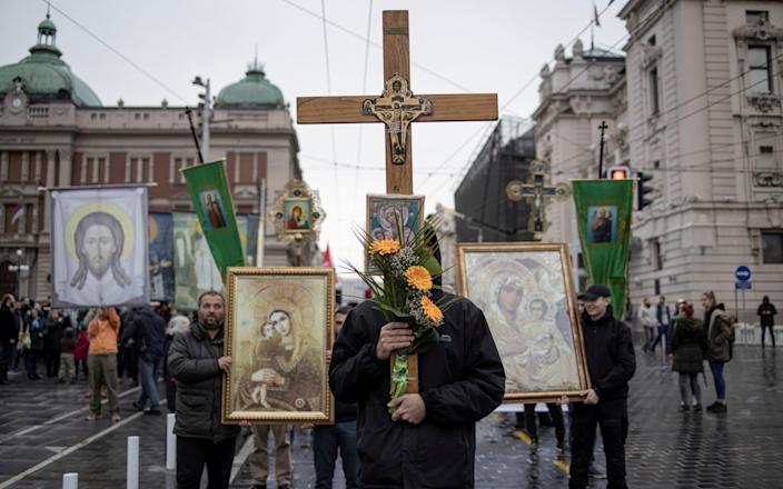 People have the Orthodox Icon when participating in protests against coronavirus vaccination and restriction in Belgrade-Reuters