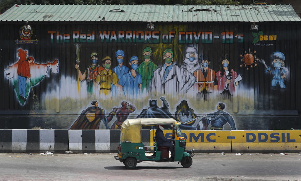 An auto rickshaw drives past a mural depicting frontline workers fighting against COVID-19 in New Delhi, India, Tuesday, Sept. 1, 2020. India has now reported more than 75,000 infections for five straight days, one of the highest in the world, just as the government began easing restrictions to help the battered economy. (AP Photo/Manish Swarup)