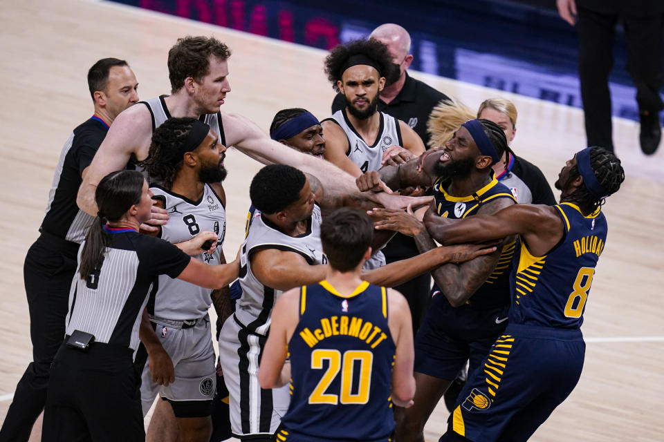 Indiana Pacers forward JaKarr Sampson (14) and San Antonio Spurs guard Patty Mills (8) exchange words during the second half of an NBA basketball game in Indianapolis, Monday, April 19, 2021. Sampson was ejected from the game. (AP Photo/Michael Conroy)
