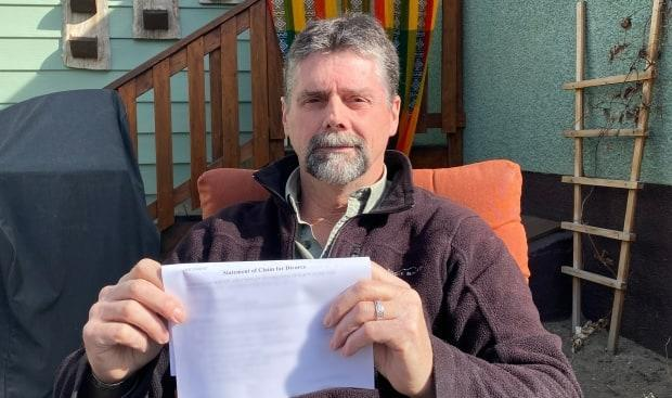 Aaron Penman holds one of the court documents a paralegal claimed had been filed with an Alberta court, only to discover the court had no record of it. (Peter Cameron-Inglis/CBC - image credit)