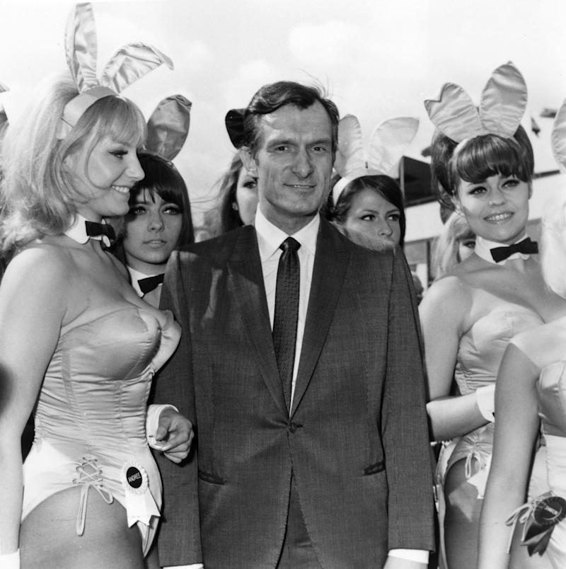 "Playboy editor and tycoon Hugh Hefner is greeted by a group of ""bunny"" girls from his Playboy Clubs upon his arrival at London Airport. (Dove via Getty Images)"