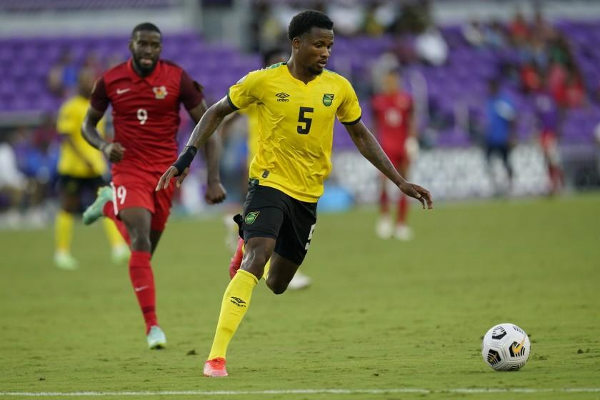 Jamaica defender Alvas Powell (5) moves the ball ahead of Guadeloupe forward Raphael Mirval (9) during the second half of a CONCACAF Gold Cup Group C soccer match, Friday, July 16, 2021, in Orlando, Fla. (AP Photo/John Raoux)