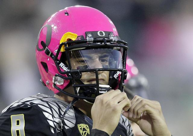 Oregon quarterback Marcus Mariota adjusts the strap on his pink helmet before an NCAA college football game against Washington State in Eugene, Ore., Saturday, Oct. 19, 2013. (AP Photo/Don Ryan)