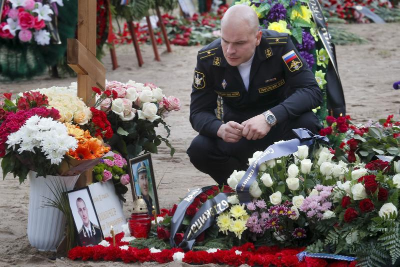 A Russian navy officer pays his last respect at the grave of Captain 3rd rank Vladimir Sukhinichev, one of the 14 crew members who died in a fire on a Russian navy's deep-sea research submersible, at the Serafimovskoye memorial cemetery during a funeral ceremony in St. Petersburg, Russia, Saturday, July 6, 2019. Russian President Vladimir Putin has awarded the nation's highest honors to 14 seamen who died in a fire on one of the navy's research submersibles. (AP Photo/Dmitri Lovetsky)