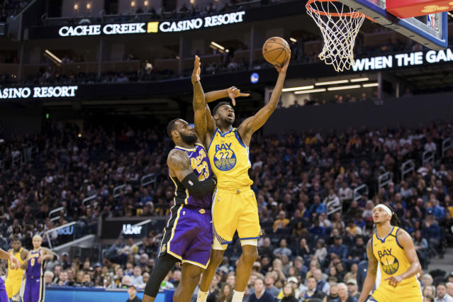 Golden State Warriors guard Andrew Wiggins shoots as Los Angeles Lakers forward LeBron James defends him in the second half on Saturday in San Francisco. The Lakers won 125-120. (AP/John Hefti)
