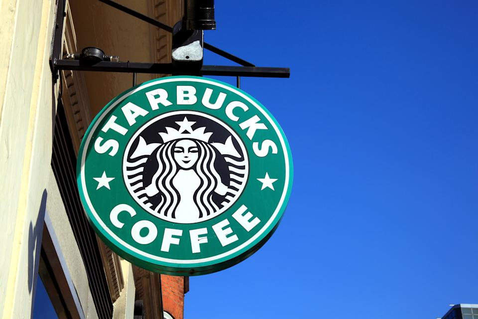 London, United Kingdom, Apr 9, 2011 : Starbucks green logo advertising sign hanging outside one of its coffee houses in Buckingham Palace Road near Victoria Station