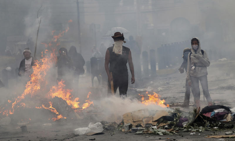 Anti-government protesters stand behind their burning roadblock as they face off with police near the National Assembly during a military curfew in Quito, Ecuador, Sunday, Oct. 13, 2019. Deadly protests against a plan to remove fuel subsidies as part of an International Monetary Fund austerity package have gone on for more than a week. (AP Photo/Dolores Ochoa)