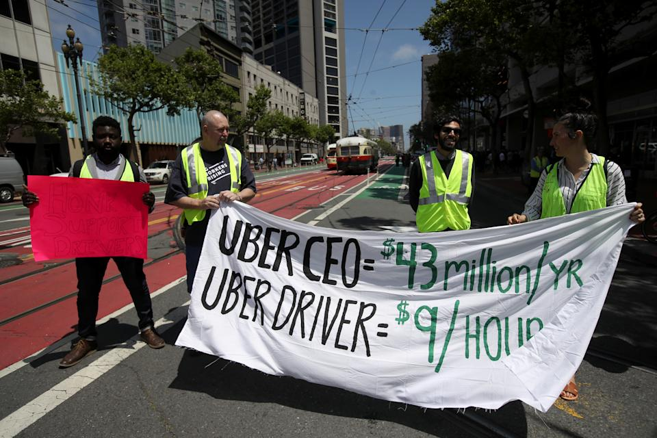 SAN FRANCISCO, CA - MAY 08: Supporters of ride share drivers from Uber and Lyft hold a sign during a protest in front of Uber headquarters on May 08, 2019 in San Francisco, California. The protests in more than a dozen cities come ahead of Uber's anticipated Initial Public Offering on the New York Stock Exchange (NYSE) which could put the ride-hailing firm's calculation as high as $91.5 billion. Drivers are seeking higher wages and better rights as employees. (Photo by Justin Sullivan/Getty Images)