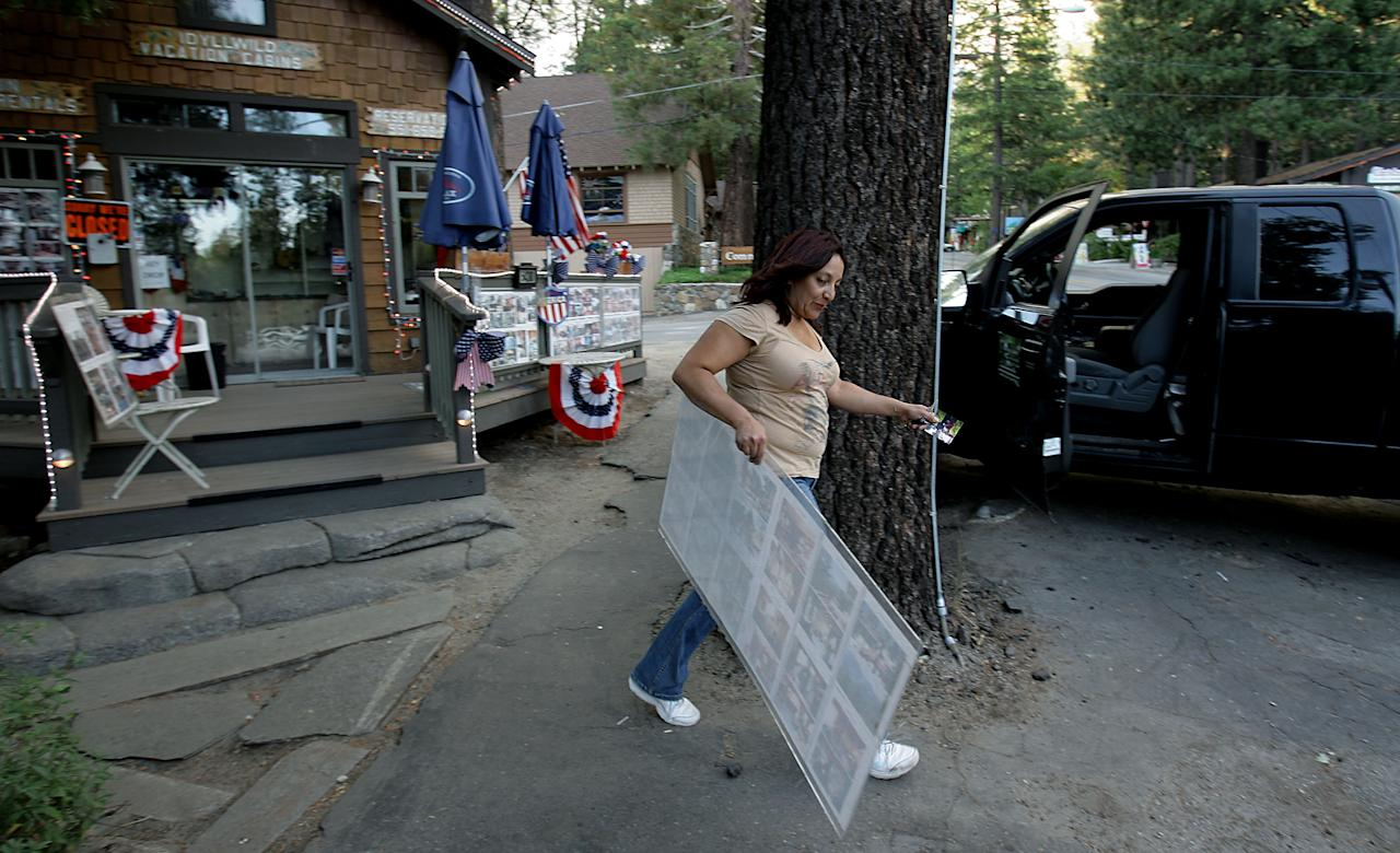 Idyllwild Vacation Cabins owner Martha Sanchez piles the last of her belongings into her truck as she evacuates Idyllwild as the The Mountain Fire burns closer to the city of Idyllwild, Calif., Wednesday July 17, 2013. Large parts of the Southern California communities of Idyllwild and Fern Valley were under evacuation orders with an estimated 300 to 400 homes affected, U.S. Forest Service spokeswoman Carol Jandrall said. (AP Photo/The Press-Enterprise, Terry Pierson)
