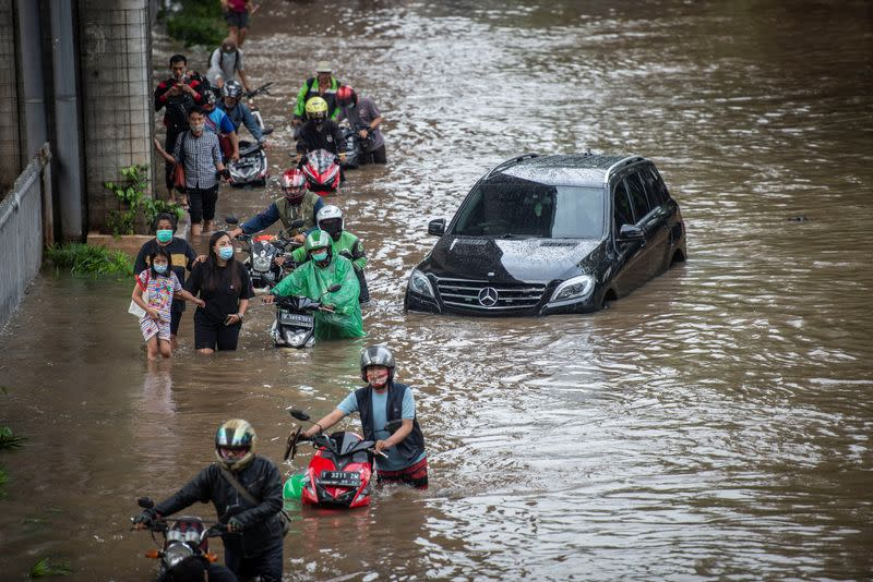 People push their motorbikes through water in an area affected by floods following heavy rains in Jakarta