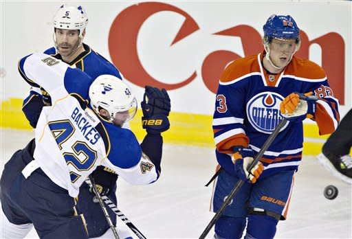 St. Louis Blues' David Backes, 42, bats the puck out of the air as Barret Jackman, 5, and Edmonton Oilers' Ales Hemsky, 83, look for the puck during first period NHL hockey action in Edmonton, Alberta, on Saturday March 23, 2013. (AP Photo/The Canadian Press, Jason Franson)