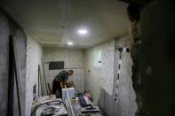 Alberto Gogu places pieces of ceramic tile on the back wall of his future indoor bathroom