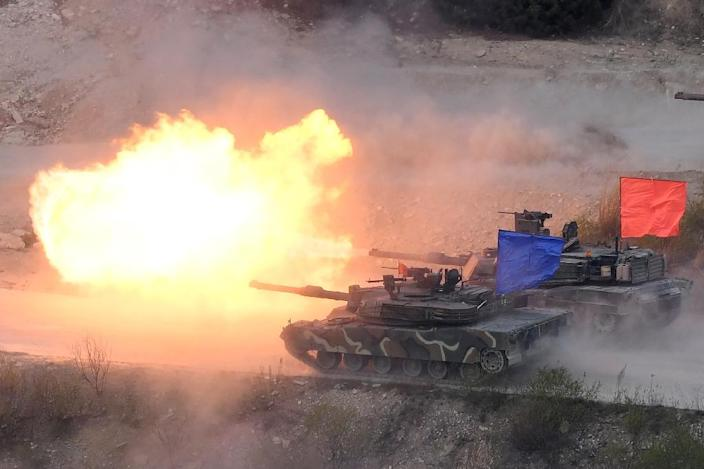 A South Korean K1A2 tank (blue) and a US M1A2 tank (red) fire live rounds during a joint drill at the Seungjin Fire Training Field northeast of Seoul (AFP Photo/JUNG YEON-JE)