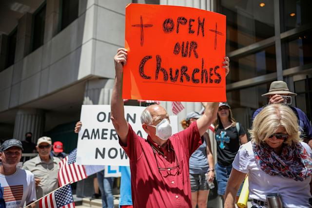 Demonstrators holding signs demanding the reopening of churches during a rally on May 1, 2020, in San Diego. (Photo: SANDY HUFFAKER via Getty Images)