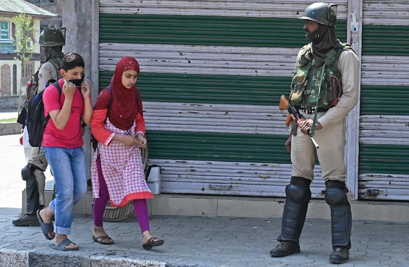 Kashmiri students walks past Indian paramilitary troopers in Srinagar during a general strike (AFP Photo/TAUSEEF MUSTAFA)