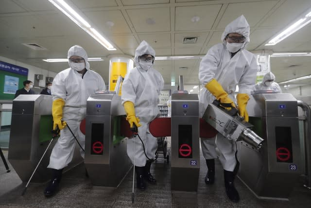 Workers spray disinfectant at a subway station in Seoul