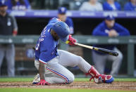 Texas Rangers' Adolis Garcia falls in the batter's box after swinging at a pitch from the Colorado Rockies during the third inning of a baseball game Wednesday, June 2, 2021, in Denver. (AP Photo/David Zalubowski)