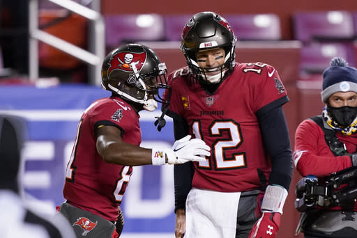 Tampa Bay Buccaneers wide receiver Antonio Brown (81) celebrating his touchdown with teammate quarterback Tom Brady (12) during the first half of an NFL wild-card playoff football game against the Washington Football Team, Saturday, Jan. 9, 2021, in Landover, Md. (AP Photo/Andrew Harnik)