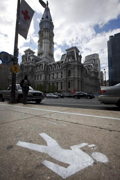 """FILE - An April 2, 2012 file photo shows an """"e-lane"""" sidewalk graphic displayed in view of City Hall, in Philadelphia. Philadelphia Mayor Michael Nutter used April Fool's Day to have a little fun with what he says is a real problem: distracted walking. City officials painted lines and oblivious stick-figure pictures on one stretch of John F. Kennedy Boulevard near City Hall as a jab at pedestrians who keep their eyes on their cellphone screens and not their surroundings. Across the country on city streets, in suburban parking lots and in shopping centers, there is usually someone strolling while talking on a phone, texting with their head down, listening to music, or playing a video game. The problem isn't as widely discussed as distracted driving, but the danger is real. (AP Photo/Matt Rourke, File)"""